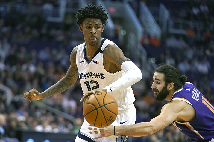 Memphis Grizzlies guard Ja Morant (12) drives against Phoenix Suns guard Ricky Rubio in the first half during an NBA basketball game, Sunday, Jan. 5, 2020, in Phoenix. (AP Photo/Rick Scuteri)