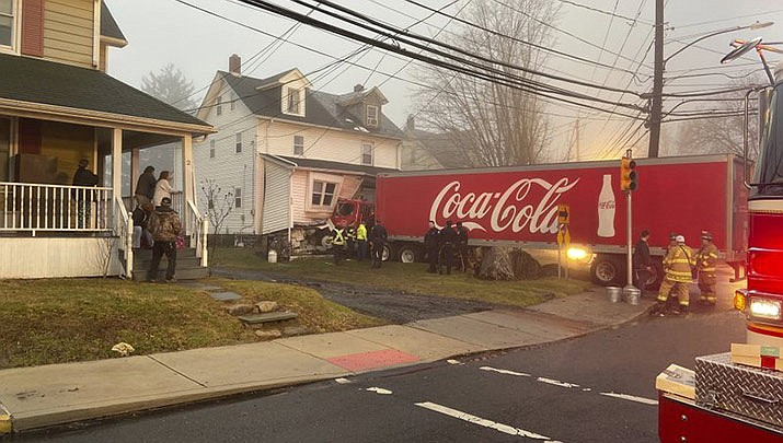 This photo provided by Jayson Wagner shows a tractor-trailer that jumped a curb and crashed into a house in suburban Philadelphia, early Saturday, Jan. 4, 20120. Officials spent Saturday morning trying to remove the bright red truck with a Coca-Cola logo on its sides from the twin home in Quakertown. Police say no one else was injured. (Jayson Wagner via AP)