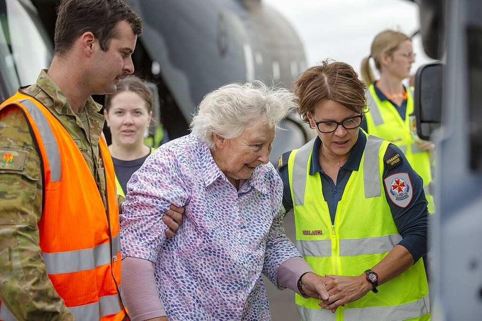 In this Jan. 5, 2020, photo provided by the Australian Department of Defence, Australian Army Soldier, Corporal Storm Sharp, left, and a paramedic, right, assist a woman at Sale after the evacuation of fire effected areas of Australia's south east. The wildfires have so far scorched an area twice the size of the U.S. state of Maryland.(Corporal Nicole Dorrett/ADF via AP)