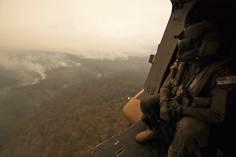 In this Sunday, Jan. 5, 2020, photo provided by Australian Department of Defence, a Royal Australian Navy MRH-90 helicopter crew member looks out over fires burning near Cann River, Australia. The wildfires have so far scorched an area twice the size of the U.S. state of Maryland. (Private Michael Currie/ADF via AP)