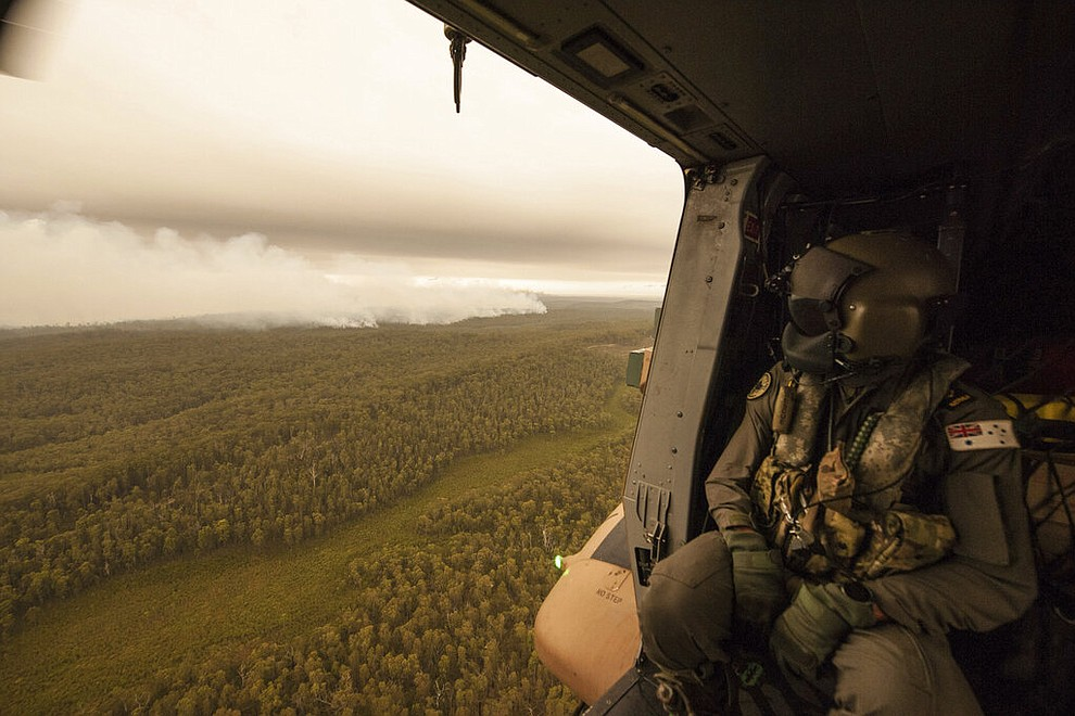 In this Sunday, Jan. 5, 2020, photo provided by Australian Department of Defence, a Royal Australian Navy MRH-90 helicopter crew member looks out over fires burning near Cann River. The wildfires have so far scorched an area twice the size of the U.S. state of Maryland. (Private Michael Currie/ADF via AP)