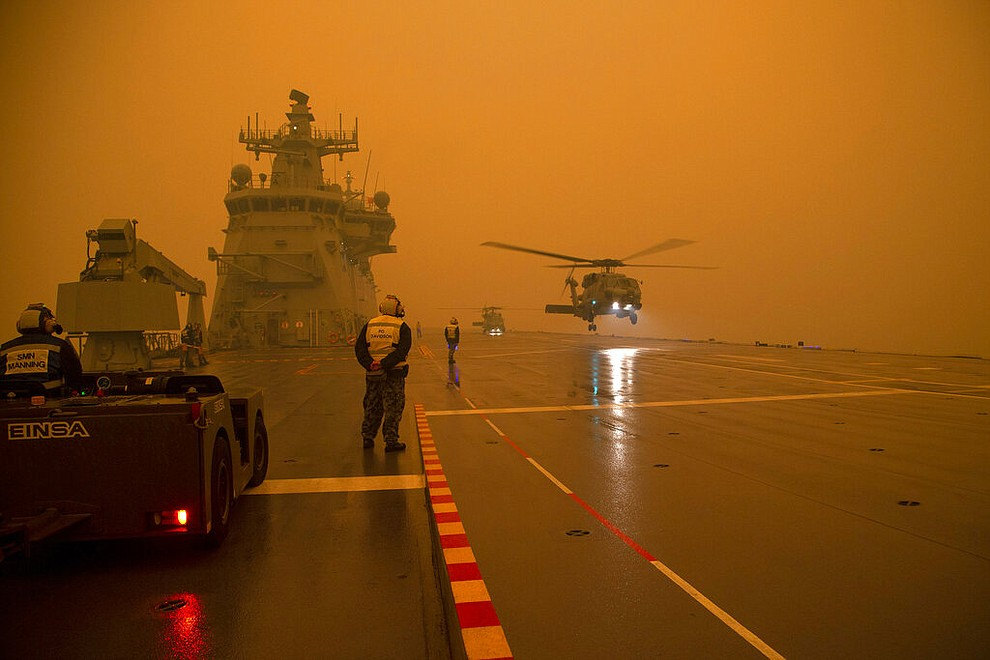 In this photo provided by the Australian Department of Defence, a Royal Australian Navy Seahawk Helicopter departs from HMAS Adelaide while at sea off Australia's east coast, Sunday, Jan. 5, 2020, during operations to assist in battling wildfires. The wildfires have so far scorched an area twice the size of the U.S. state of Maryland. (Able Seaman Thomas Sawtell/ADF via AP)