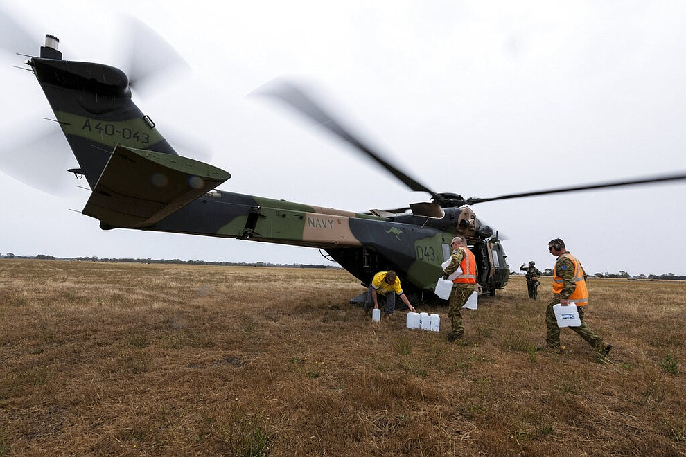 In this photo provided by the Australian Department of Defence, a Royal Australian Navy helicopter is loaded with supplies at Bairnsdale for the fire impacted community of Cann River Sunday, Jan. 5, 2020. The wildfires have so far scorched an area twice the size of the U.S. state of Maryland. (Private Michael Currie/ADF via AP)