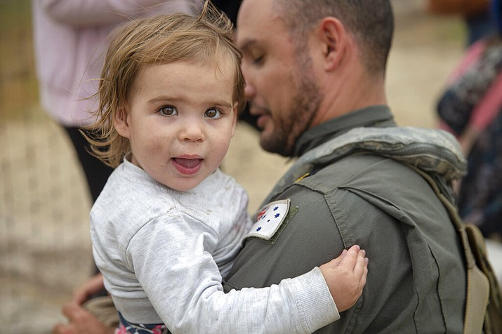 In this photo provided by the Australian Department of Defence, a child is helped onto a helicopter as the fire ravaged community of Mallacoota is evacuated, Sunday, Jan. 5, 2020. The wildfires have so far scorched an area twice the size of the U.S. state of Maryland. (Corporal Nicole Dorrett/ADF via AP)