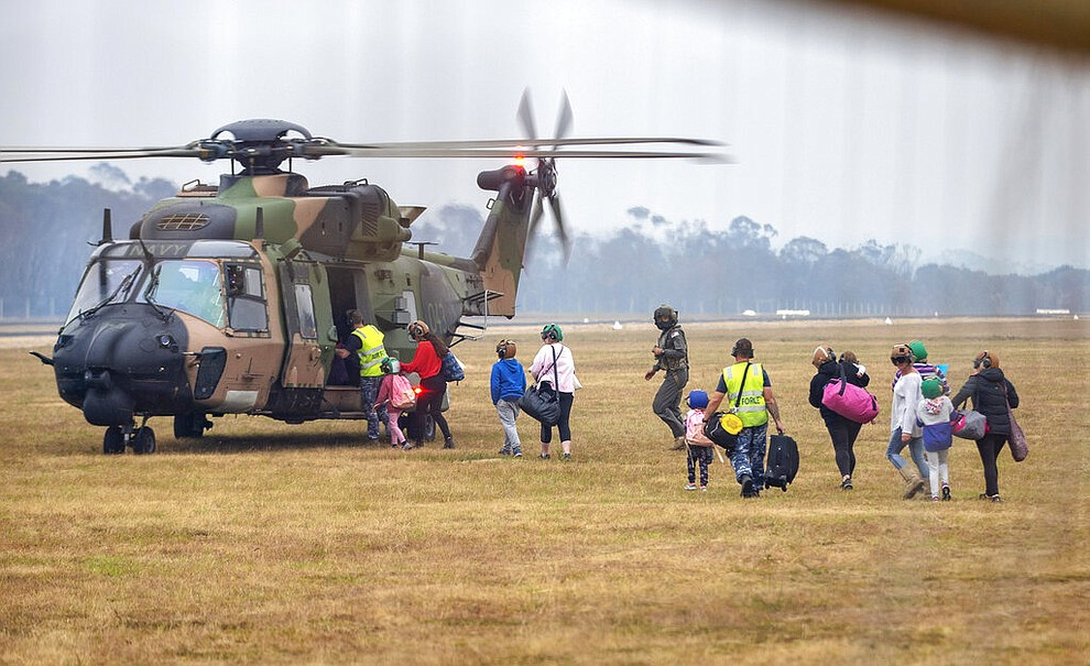 In this photo provided by the Australian Department of Defence, people walk to board a helicopter as the fire ravaged community of Mallacoota is evacuated, Sunday, Jan. 5, 2020. The wildfires have so far scorched an area twice the size of the U.S. state of Maryland.  (Corporal Nicole Dorrett/ADF via AP)
