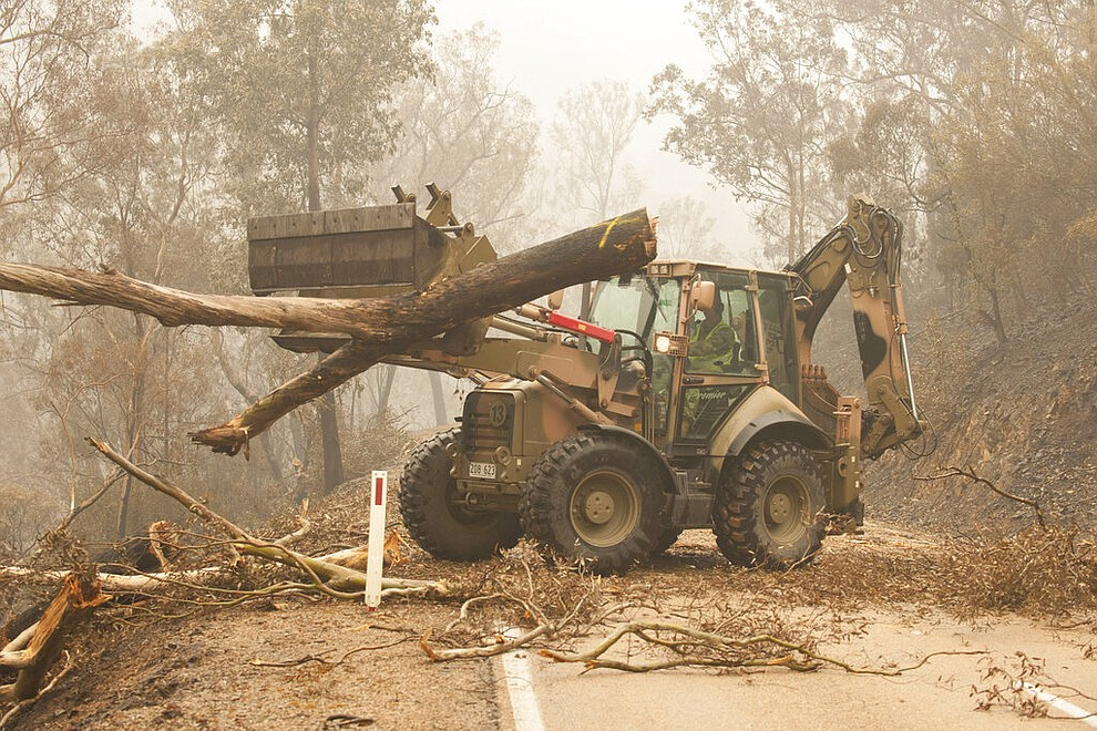 """In this image released and dated on Jan. 6, 2020, from Australian Department of Defence, plant operators Cpl. Duncan Keith and Sapper Ian Larner of the 22nd Engineer Regiment use a 434 backhoe to assist staff from Forestry Management Victoria to clear fire damaged trees from the great Alpine road between Bairnsdale and Omeo during Operation Bushfire Assist 19-20 in Bairnsdale, Victoria, Australia. Australia's government on Monday said it was willing to pay """"whatever it takes"""" to help communities recover from deadly wildfires that have ravaged the country. (Department of Defence via AP)"""