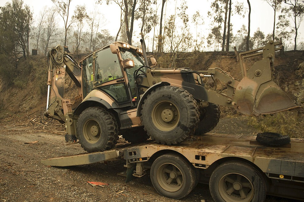 """In the image released and dated Monday, Jan. 6, 2020, by the Australian Department of Defence, plant operators Cpl. Duncan Keith and Sapper Ian Larner of the 22nd Engineer Regiment use a 434 backhoe to assist staff from Forestry Management Victoria to clear fire damaged trees from the great Alpine road between Bairnsdale and Omeo during Operation Bushfire Assist 19-20 in Bairnsdale, Victoria, Australia. Australia's government on Monday said it was willing to pay """"whatever it takes"""" to help communities recover from deadly wildfires that have ravaged the country. (Australia Department of Defence via AP)"""