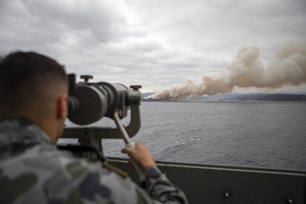 In this photo provided by the Australian Department of Defence on Jan. 6, 2020, Seaman Boatswains Mate Malik El-Leissy watches a burning fire from HMAS Adelaide as the ship arrives at Eden to assist with wildfires. The wildfires have so far scorched an area twice the size of the U.S. state of Maryland. They have destroyed about 2,000 homes. (Able Seaman Thomas Sawtell/ADF via AP)