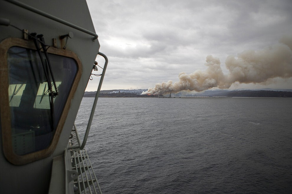 In this photo provided by the Australian Department of Defence on Jan. 6, 2020, a fire burns near Eden as HMAS Adelaide arrives to assist with wildfires. The wildfires have so far scorched an area twice the size of the U.S. state of Maryland. They have destroyed about 2,000 homes. (Able Seaman Thomas Sawtell/ADF via AP)