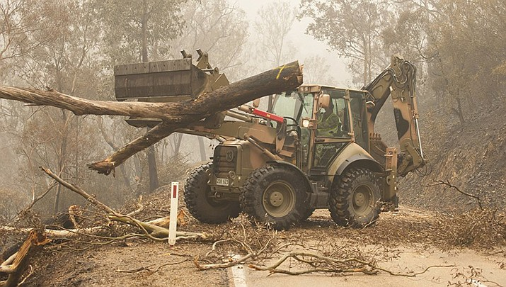 "In this image released and dated on Jan. 6, 2020, from the Australian Department of Defense, members of the 22nd Engineer Regiment use a 434 backhoe to assist staff from Forestry Management Victoria to clear fire-damaged trees from the Great Alpine Road between Bairnsdale and Omeo, Victoria, Australia. Australia's government on Monday said it was willing to pay ""whatever it takes"" to help communities recover from deadly wildfires that have ravaged the country. (Australia Department of Defense photo)"