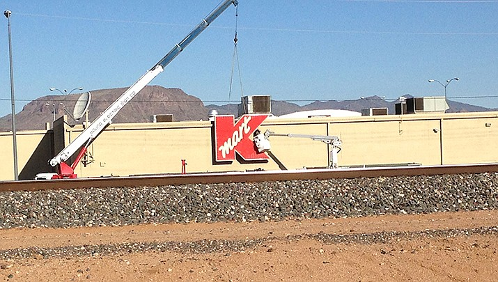 Workers are shown removing the Kmart sign from Kingman Plaza after the store closed in 2017. The owners of the complex are offering a $1,000 reward for information that leads to the arrest and conviction of the person or persons who have been breaking windows in the empty plaza. (Miner file photo)