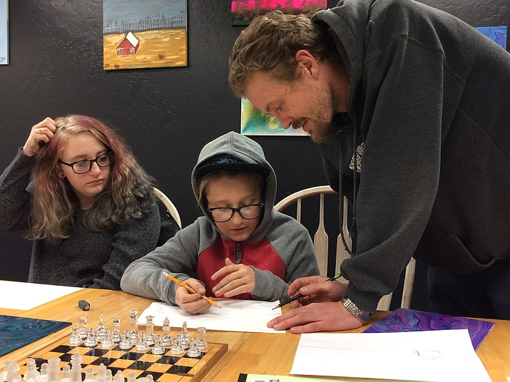 Abigail York looks as Dale Hormuth helps Damian York with a barn landscape drawing during a Friday, Dec. 27, 2019, class at Crooked Canes Art & More. (Jason Wheeler/Review)