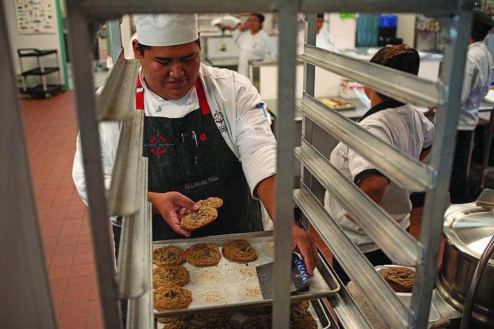 NTU Professional Baking graduate Shawn Curley removes a cookie sheet during class in 2016. NTU's Professional Baking and Culinary Arts programs were granted re-accreditation for five years in November. (Photo/NTU)