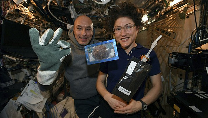 In this photo made available by U.S. astronaut Christina Koch via Twitter on Dec. 26, 2019, she and Italian astronaut Luca Parmitano pose for a photo with a cookie baked on the International Space Station. Researchers want to inspect the handful of chocolate chip cookies baked by astronauts in a special Zero G oven. (NASA photo)
