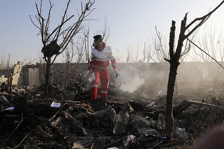 A rescue worker searches the scene where an Ukrainian plane crashed in Shahedshahr, southwest of the capital Tehran, Iran, Wednesday, Jan. 8, 2020. A Ukrainian airplane carrying 176 people crashed on Wednesday shortly after takeoff from Tehran's main airport, killing all onboard. (Ebrahim Noroozi/AP)