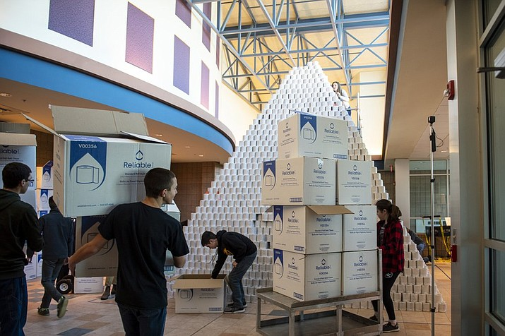 People involved in the Bullock Creek High School Robotics team prepare to take down the world's largest toilet paper pyramid on Monday, Jan. 6, 2020. Bullock Creek High School's Robotics team built the world's largest toilet paper pyramid and are selling the toilet paper back to the community for a discounted price as a fundraiser for the team.(Kaytie Boomer/The Bay City Times via AP)