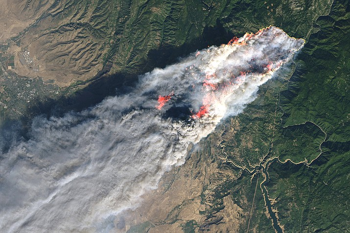 This November 2018 image provided by NASA shows flames and smoke from the Camp Fire that erupted 90 miles (140 kilometers) north of Sacramento, Calif. Increasingly intense wildfires that have scorched forests from California to Australia are stoking worry about long-term health impacts from smoke exposure in affected cities and towns. (NASA via AP)