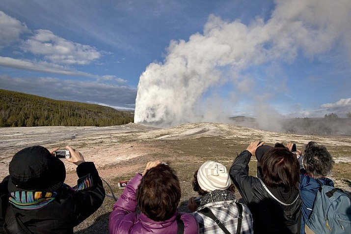 In this May 21, 2011, file photo, tourists photograph Old Faithful erupting on schedule late in the afternoon in Yellowstone National Park, Wyo. Two men who pleaded guilty to trespassing on the cone of Old Faithful Geyser in Yellowstone National Park were sentenced to 10 days in jail and have been banned from the park for five years. Eric Schefflin, 20, of Lakewood, Colo., and Ryan Goetz. 25, of Woodstock, N.Y., were sentenced on Dec. 5 by U.S. Magistrate Mark Carman in Mammoth Hot Springs, park officials announced Thursday, Jan. 9, 2020.(AP Photo/Julie Jacobson, File)