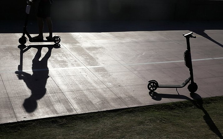 In this May 28, 2019, file photo, a man on a scooter passes a parked scooter along the Mission Beach boardwalk in San Diego. Electric scooter injuries have surged along with their popularity in the United States, nearly tripling over four years, researchers said in a study published Wednesday, Jan. 8, 2020. (AP Photo/Gregory Bull, File)