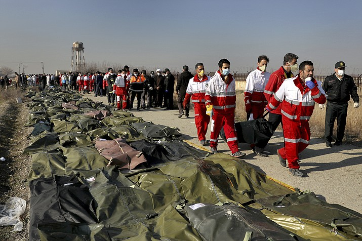 """In this Wednesday, Jan. 8 photo, rescue workers carry the body of a victim of a Ukrainian plane crash in Shahedshahr, southwest of the capital Tehran, Iran. Two U.S. officials said Thursday that it was """"highly likely"""" that an Iranian anti-aircraft missile downed a Ukrainian jetliner late Tuesday, killing all 176 people on board. President Donald Trump is suggesting he believes Iran was responsible. (Ebrahim Noroozi/AP)"""