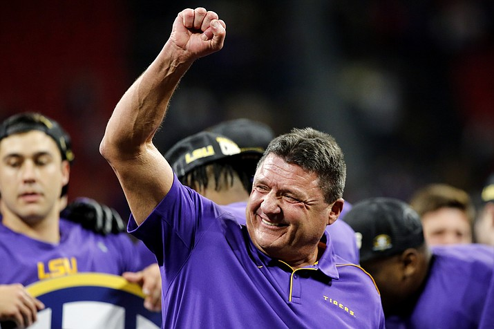 In this Dec. 7, 2019, file photo, LSU coach Ed Orgeron celebrates on stage after the team's win over Georgia in an NCAA college football game for the Southeastern Conference championship, in Atlanta. Cajun pride is swelling in Lafourche Parish now that the former two-way football standout who won a 1977 state title for the South Lafourche High School Tarpons is on the brink of capping off arguably the LSU Tigers' greatest season in the program's 126-year history with a national title. (C.B. Schmelter/Chattanooga Times Free Press via AP, File)