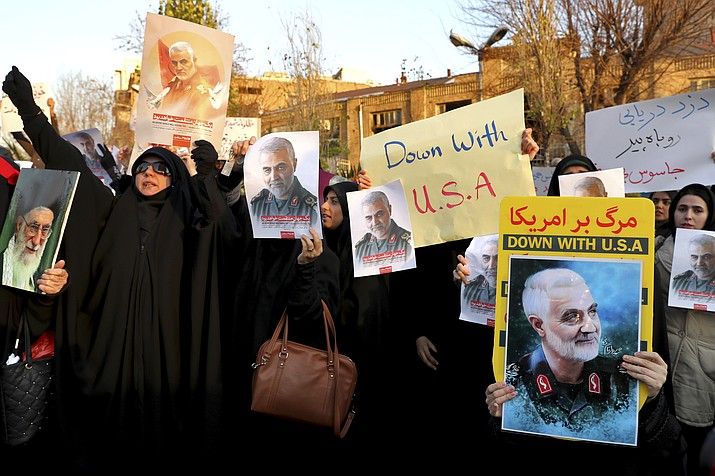 Protesters chant slogans and hold up posters of Gen. Qassem Soleimani during a demonstration in front of the British Embassy in Tehran, Iran, Sunday, Jan. 12, 2020. A candlelight ceremony late Saturday in Tehran turned into a protest, with hundreds of people chanting against the country's leaders — including Supreme Leader Ayatollah Ali Khamenei — and police dispersing them with tear gas. Police briefly detained the British ambassador to Iran, Rob Macaire, who said he went to the Saturday vigil without knowing it would turn into a protest. (AP Photo/Ebrahim Noroozi)
