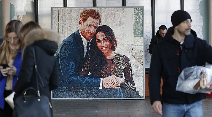 """People walk past a picture of Britain's Prince Harry and Meghan Duchess of Sussex, in Windsor, Friday, Jan. 10, 2020. Britain's Prince Harry and his wife, Meghan, said they are planning """"to step back"""" as senior members of the royal family and """"work to become financially independent."""" (AP Photo/Frank Augstein)"""