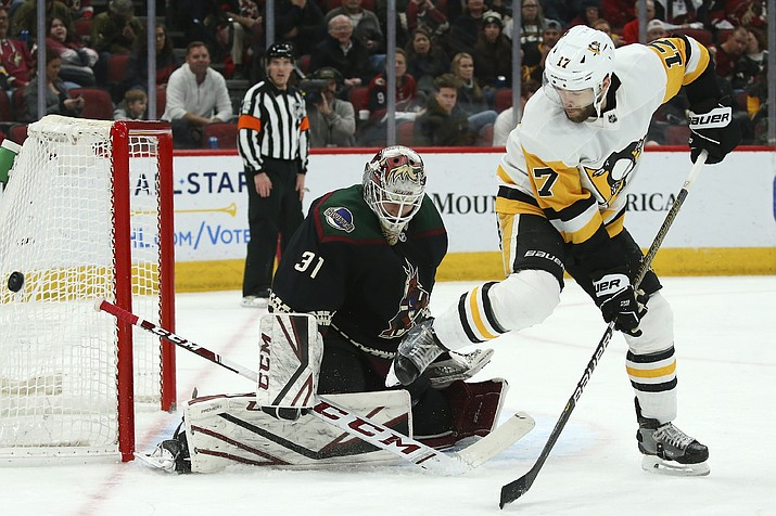 Arizona Coyotes goaltender Adin Hill (31) makes a save on a shot as Pittsburgh Penguins right wing Bryan Rust (17) gets out of the way of the shot during the second period of an NHL hockey game Sunday, Jan. 12, 2020, in Glendale, Ariz. (Ross D. Franklin/AP)