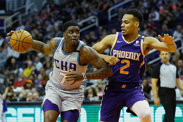 Charlotte Hornets guard Dwayne Bacon drives on Phoenix Suns forward Elie Okobo (2) during the first half of an NBA basketball game Sunday, Jan. 12, 2020, in Phoenix. (AP Photo/Rick Scuteri)