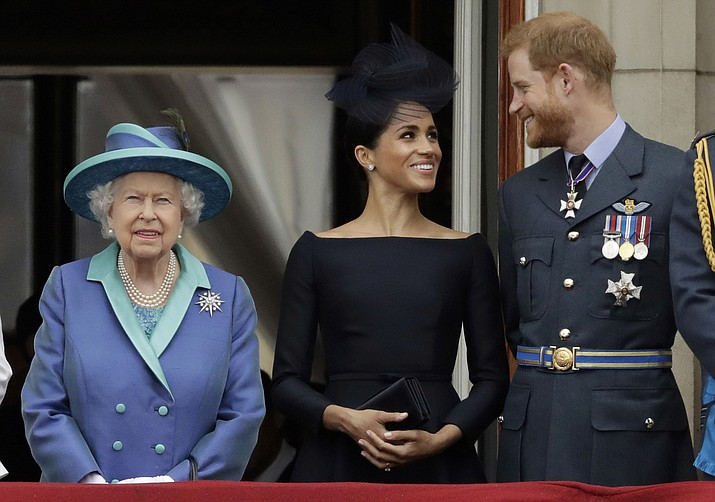 "In this Tuesday, July 10, 2018 file photo Britain's Queen Elizabeth II, and Meghan the Duchess of Sussex and Prince Harry watch a flypast of Royal Air Force aircraft pass over Buckingham Palace in London. As part of a surprise announcement distancing themselves from the British royal family, Prince Harry and his wife Meghan declared they will ""work to become financially independent"" _ a move that has not been clearly spelled out and could be fraught with obstacles. (AP Photo/Matt Dunham, File)"