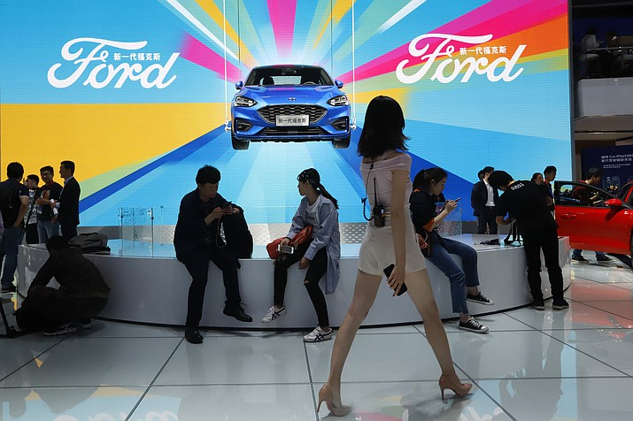 In this April 25, 2018, file photo, attendees visit the Ford booth during Auto China 2018 show held in Beijing, China. China's government says it will postpone planned punitive tariffs on U.S.-made automobiles and other goods following an interim trade deal with Washington.Sunday, Dec. 15, 2019's announcement came after Washington agreed to postpone a planned tariff hike on $160 billion of Chinese goods and to cut in half penalties that already were imposed. (AP Photo/Ng Han Guan, File)