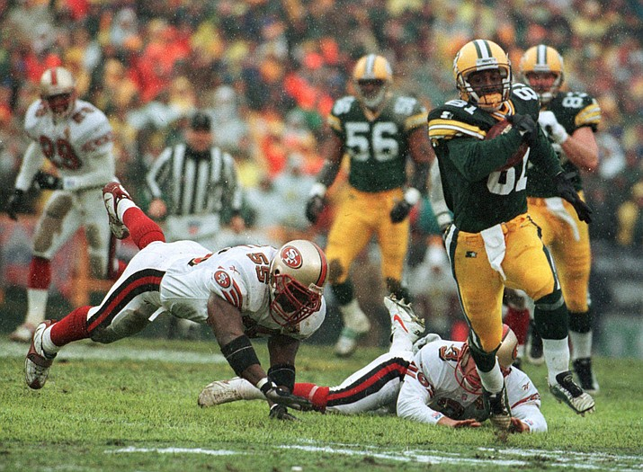 In this Jan. 4, 1997, file photo, Green Bay Packers' Desmond Howard eludes San Francisco 49ers Kevin Mitchell (55) and punter Tommy Thompson on the way to a touchdown on a punt return in the first half of an NL football game in Green Bay, Wisc. The two teams that have combined for nine Super Bowl titles will meet with a spot in the ultimate game on the line once again when the 49ers (14-3) host the Packers (14-3) in the NFC championship game on Sunday, Jan. 19, 2020.(David Boe/AP, file)