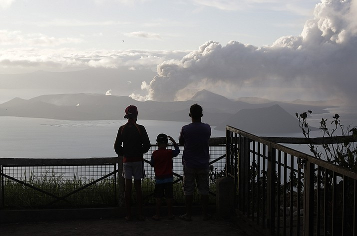 People watch from Tagaytay, Cavite province, south of Manila, as Taal Volcano continues to spew ash on Tuesday, Jan. 14, 2020. Thousands of people fled the area through heavy ash as experts warned that the eruption could get worse and plans were being made to evacuate more. (Aaron Favila/AP)