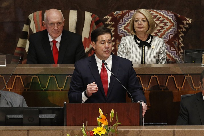 Arizona Republican Gov. Doug Ducey speaks during his State of the State address about Arizona's economy, new jobs, prison reform, and education as Senate president Karen Fann, R-Prescott, right, and House Speaker Rusty Bowers, R-Mesa, left, listen in on the opening day of the legislative session at the Capitol, Monday, Jan. 13, 2020, in Phoenix. (AP Photo/Ross D. Franklin)