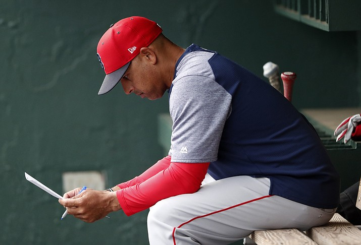 In this March 20, 2019, file photo, Boston Red Sox manager Alex Cora looks over the lineup before the team's spring training baseball game against the Baltimore Orioles in Sarasota, Fla. Cora was fired by the Red Sox on Tuesday, Jan. 14, 2020, a day after baseball Commissioner Rob Manfred implicated him in the sport's sign-stealing scandal. (John Bazemore/AP, file)