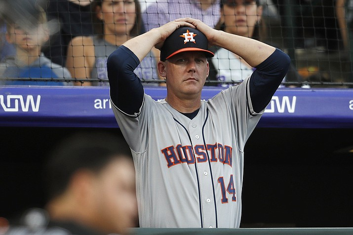 In this July 2, 2019, file photo, Houston Astros manager AJ Hinch reacts during a baseball game against the Colorado Rockies, in Denver. Houston manager AJ Hinch and general manager Jeff Luhnow were suspended for the entire season Monday, Jan. 13, 2020, and the team was fined $5 million for sign-stealing by the team in 2017 and 2018 season. Commissioner Rob Manfred announced the discipline and strongly hinted that current Boston manager Alex Cora — the Astros bench coach in 2017 — will face punishment later. Manfred said Cora developed the sign-stealing system used by the Astros. (David Zalubowski/AP, file)