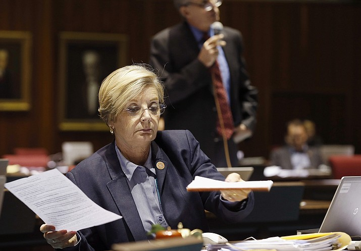 In this May 3, 2016, file photo Rep. Karen Fann, R-Prescott, goes over paperwork during budget deliberations at the Arizona Capitol in Phoenix. An Arizona Senate committee has delayed consideration of a contentious proposal from a conservative Republican lawmaker that would bar any sexual education instruction for students before 7th grade. (Ross D. Franklin/AP, file)