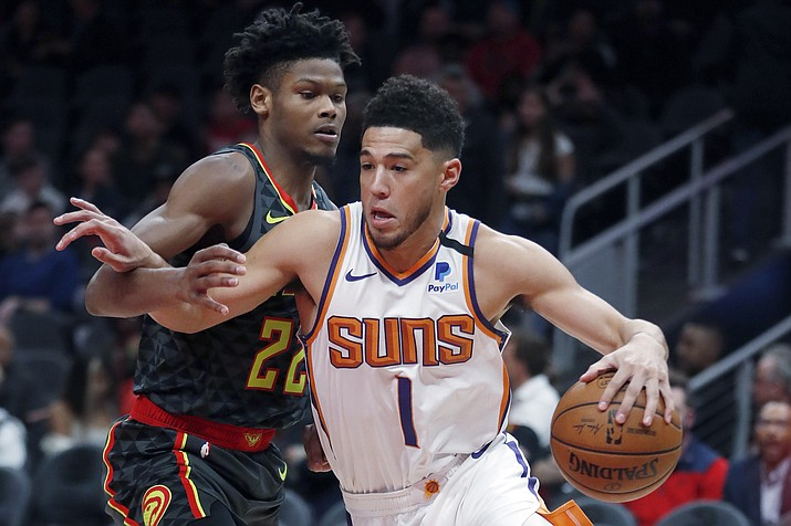 Phoenix Suns guard Devin Booker (1) drives against Atlanta Hawks forward Cam Reddish (22) in the first half of an NBA basketball game Tuesday, Jan. 14, 2020, in Atlanta. (John Bazemore/AP)