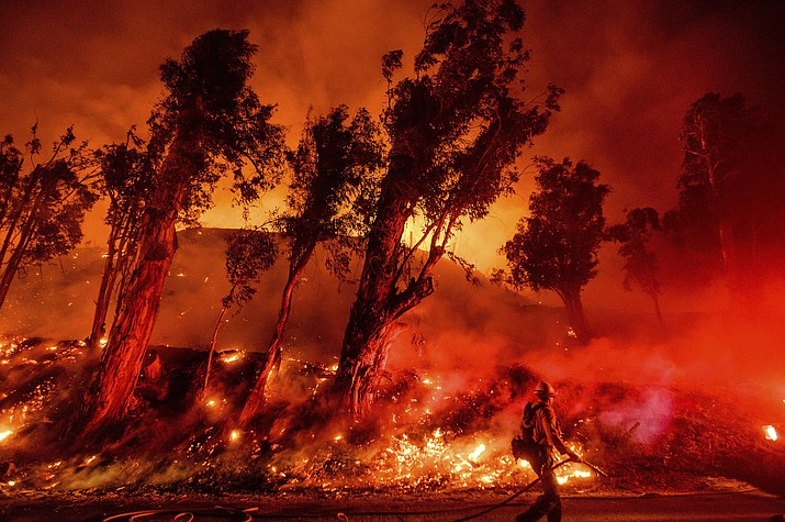 In this Nov. 1, 2019, file photo, flames from a backfire consume a hillside as firefighters battle the Maria Fire in Santa Paula, Calif. The decade that just ended was by far the hottest ever measured on Earth, capped off by the second-warmest year on record, NASA and the National Oceanic and Atmospheric Administration reported Wednesday, Jan. 15, 2020. (Noah Berger/AP, file)