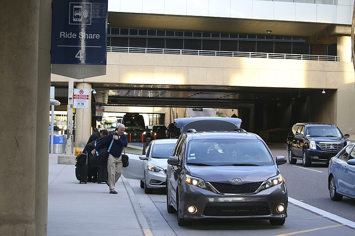 """In this Dec. 18, 2019 photo, passengers find their rides at the Ride Share point as they exit Phoenix Sky Harbor International Airport in Phoenix. A new $4 fee on Uber and Lyft rides to and from the Phoenix airport is """"very likely"""" unconstitutional, the state attorney general said Thursday, Jan. 16, 2020. (Ross D. Franklin/AP, File)"""