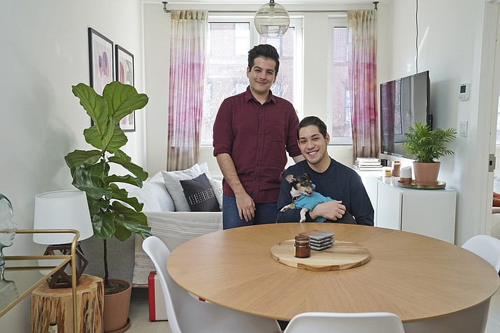 In this Monday, Nov. 25, 2019 photo, Zachariah Mohammed, left, Pete Mancilla, and their dog Remy pose for a picture in their apartment in New York. Most of the furniture in their apartment, including the couch, the table and chairs, the side table and the bar cart, are rented. Furniture-rental startups and other companies are aiming to rent furniture to millennials who don't want to commit to big purchases or move heavy furniture and are willing to pay for the convenience.   (Seth Wenig/AP, file)