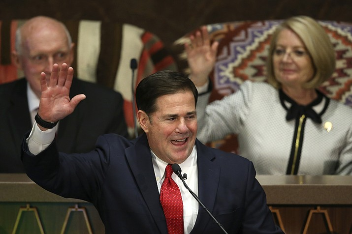 Arizona Republican Gov. Doug Ducey, front, raises his arm as he makes a pledge as he speaks during his State of the State address about Arizona's economy, new jobs, prison reform, and education as Senate president Karen Fann, R-Prescott, back right, and House Speaker Rusty Bowers, R-Mesa, back left, listen in on the opening day of the legislative session at the Capitol, Monday, Jan. 13, 2020, in Phoenix. (Ross D. Franklin/AP)