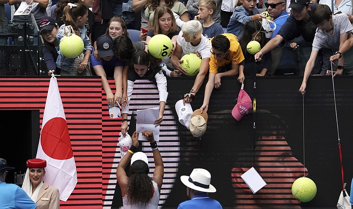 Japan's Naomi Osaka signs autographs after defeating Marie Bouzkova of the Czech Republic in their first round singles match the Australian Open tennis championship in Melbourne, Australia, Monday, Jan. 20, 2020. (AP Photo/Lee Jin-man)