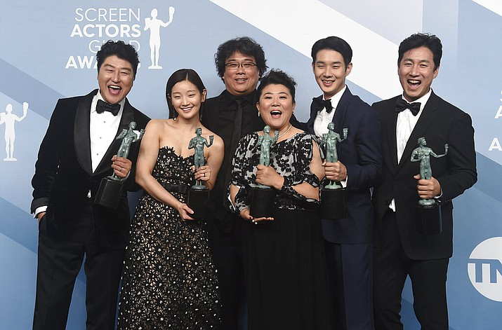 """Kang-Ho Song, from left, Park So-dam, Bong Joon-ho, Jang Hye-jin, Choi Woo-shik, and Lee Sun Gyun pose in the press room with the award for outstanding performance by a cast in a motion picture for """"Parasite"""" at the 26th annual Screen Actors Guild Awards at the Shrine Auditorium & Expo Hall on Sunday, Jan. 19, 2020, in Los Angeles. (Photo by Jordan Strauss/Invision/AP)"""