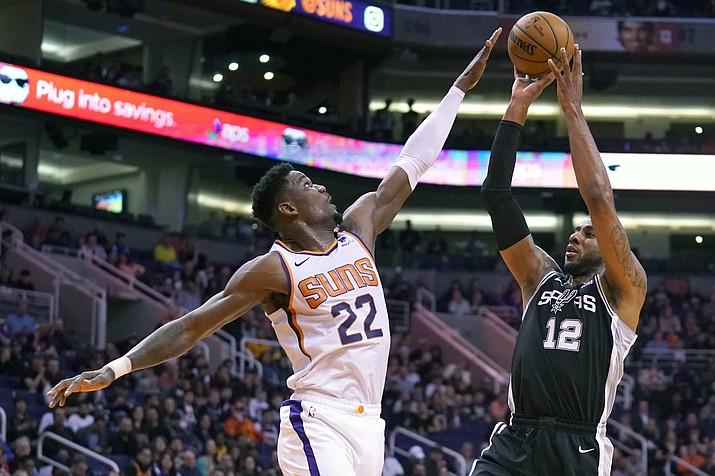 San Antonio Spurs center LaMarcus Aldridge (12) shoots over Phoenix Suns center Deandre Ayton during the first half of an NBA basketball game Monday, Jan. 20, 2020, in Phoenix. (AP Photo/Rick Scuteri)