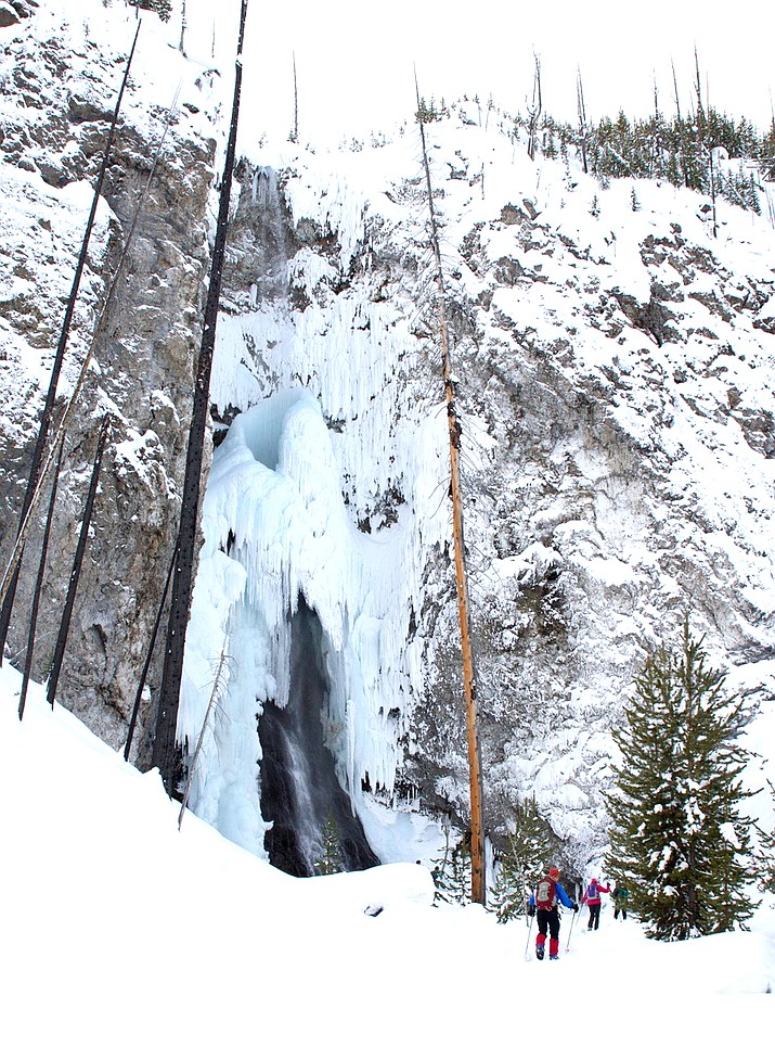 Skiing the Fairy Falls Ski Trail in winter treats visitors to an icy view of this popular 197 foot waterfall. (NPS/Diane Renkin)