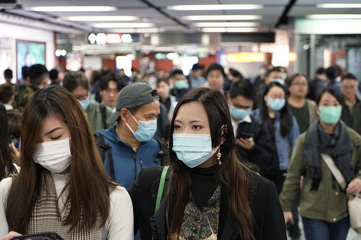 Passengers wear masks to prevent an outbreak of a new coronavirus in a subway station, in Hong Kong, Wednesday, Jan. 22, 2020. The first case of coronavirus in Macao was confirmed on Wednesday, according to state broadcaster CCTV. The infected person, a 52-year-old woman, was a traveller from Wuhan. (Kin Cheung/AP)