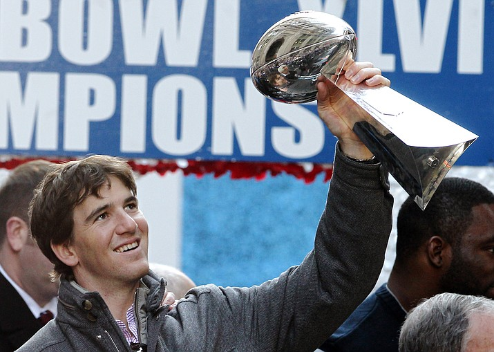 In this Feb. 7, 2012 photo, New York Giants quarterback Eli Manning holds up the Vince Lombardi Trophy during the team's Super Bowl parade in New York. (Julio Cortez/AP, file)