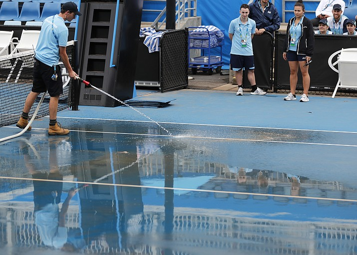 Ground staff wash red dust tainted water from an outside court as rain delayed play at the Australian Open in Melbourne, Australia, Thursday, Jan. 23, 2020. (Andy Wong/AP)