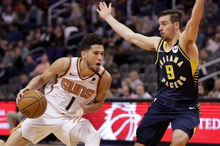 Phoenix Suns guard Devin Booker (1) drives as Indiana Pacers guard T.J. McConnell (9) defends during the second half of a game, Wednesday, Jan. 22, 2020, in Phoenix. (Matt York/AP)